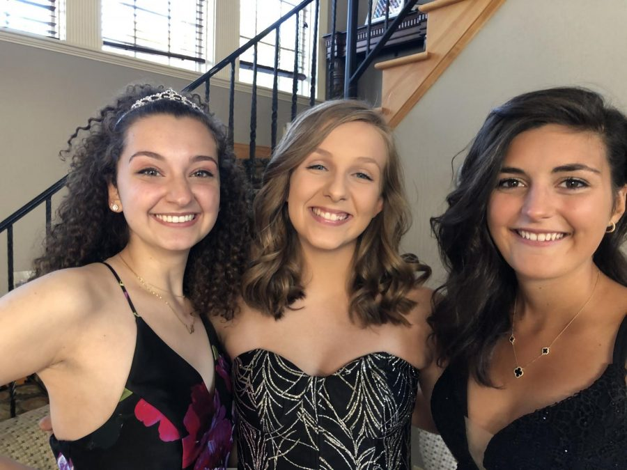 Scaccio poses with seniors Lauren Meadows and Kirsten Moore before the homecoming dance.