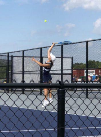Senior Anna Siesel returns the ball in her tennis match.