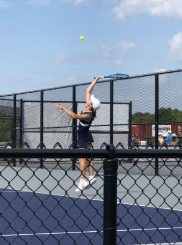 Senior Anna Siesel returns the ball in her tennis match.
