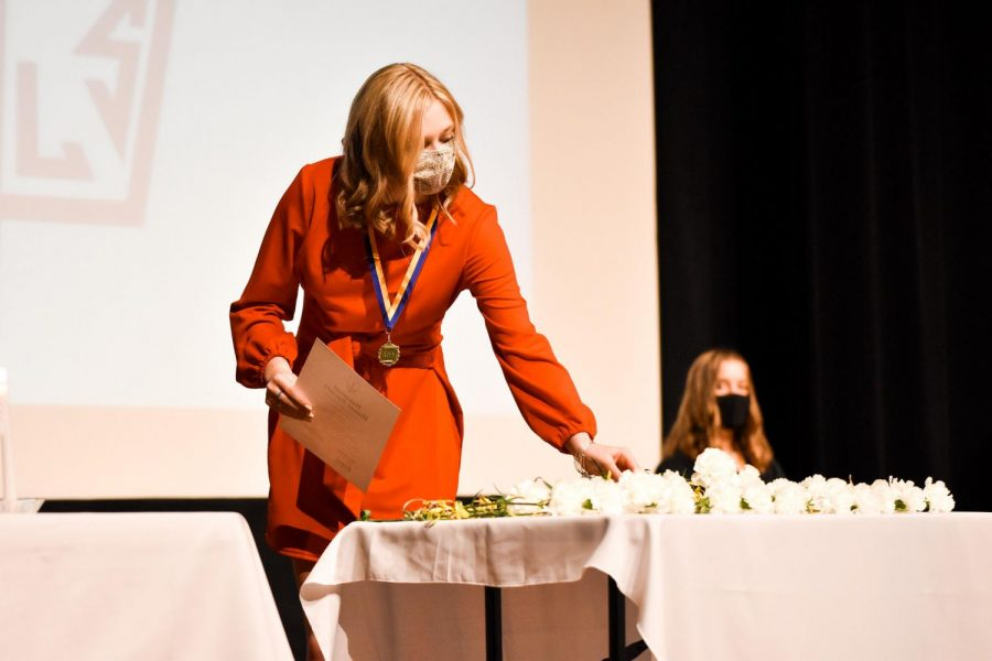Junior Ashton Bell picks up her flower as part of the Induction Ceremony Nov. 10 in the auditorium.
