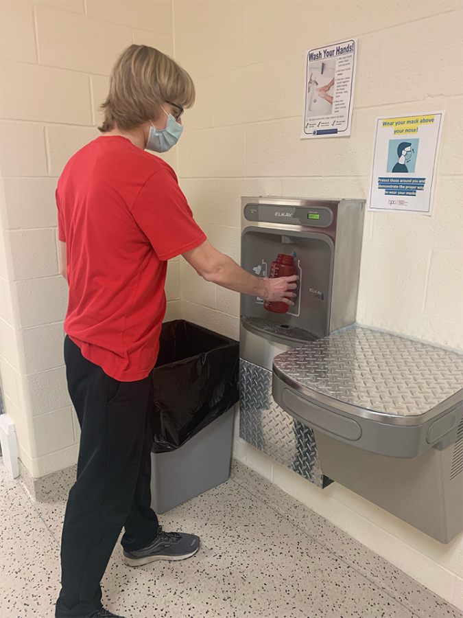 Junior Isaac Bee fills his water bottle at the new filling station in the 1600 hallway..